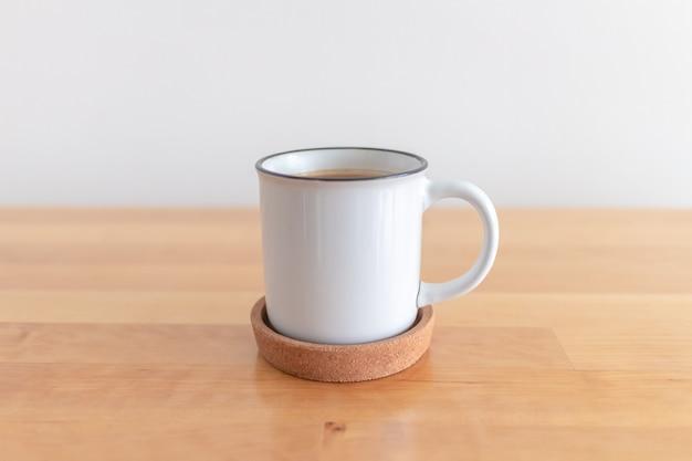 Witte kop warme koffiemok op houten tafel met witte muur