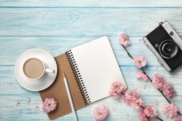 Witte kopcappuccino met sakurabloemen, notitieboekje en oude fotocamera op een blauwe houten lijst