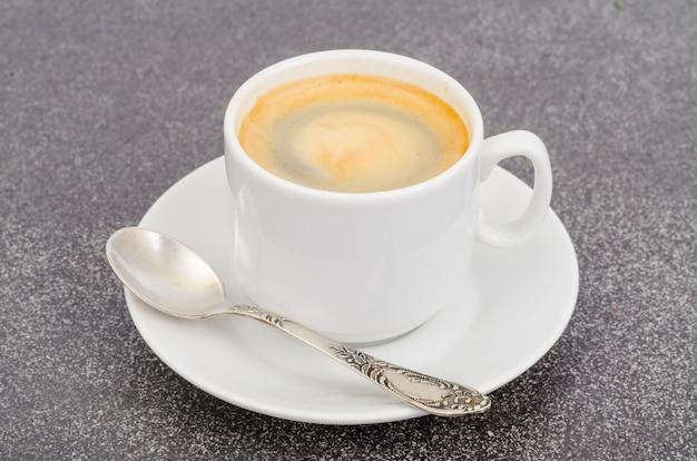 Witte kopespresso met schuim op grijze steen