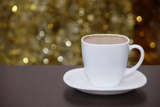 Witte kopje koffie met melk, glinsterende bokeh lichten. vieren, kerstmis, nieuwjaar, vakantie partij achtergrond.