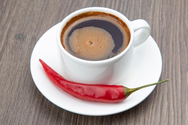 Witte kopje zwarte koffie en rode hete peper op een houten frame