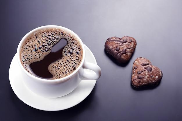 Witte kopje zwarte koffie met koekjes op een donker