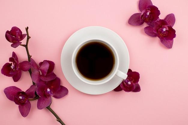 Witte kopje zwarte thee of koffie met orchideeën bloemen op een roze achtergrond.