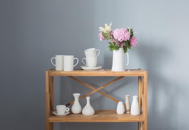 Witte kopjes en bloemen op vaas op houten plank op grijze achtergrond