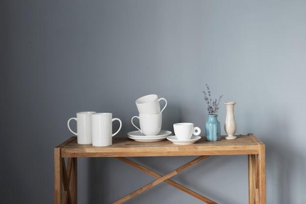 Witte kopjes en vazen op houten plank op grijze achtergrond