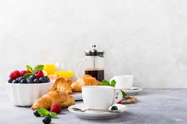 Witte kopjes koffie en croissants