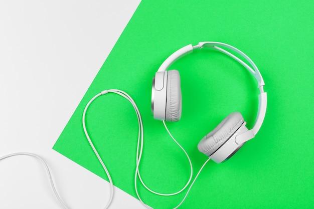 Witte koptelefoon met snoer op felgroene achtergrond