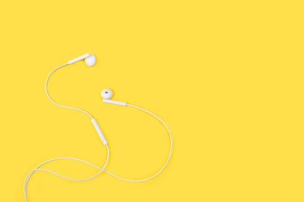Witte koptelefoon op een gele achtergrond in een bovenaanzicht