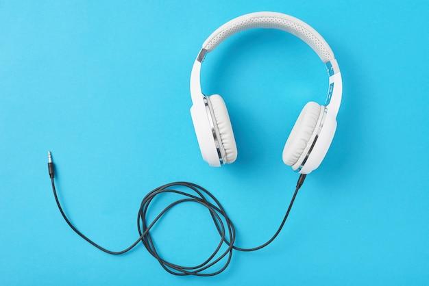 Witte koptelefoon op een pastel blauwe achtergrond