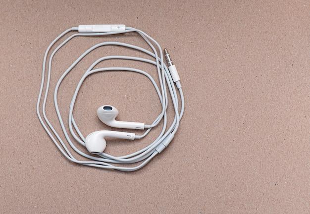 Witte koptelefoon op zacht bruin papier met ruimte voor tekst of ideeën, draad en oortelefoons