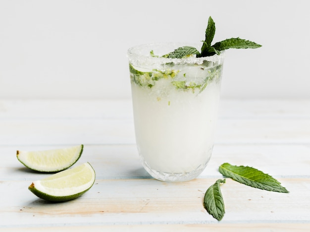 Witte koude cocktail met munt, limoen en ijs in studio
