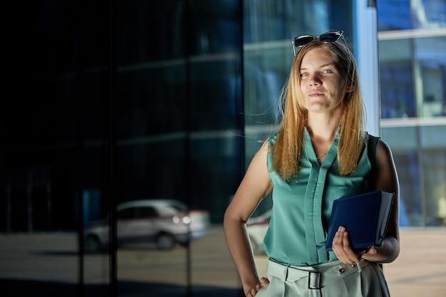 Witte kraag vrouw met notitieblok in haar hand staat buiten een kantoorgebouw of zakencentrum