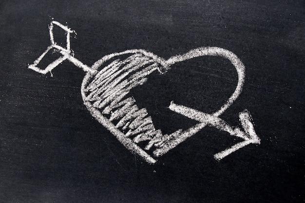 Witte krijttekening in hart met pijlvorm op zwarte raadsachtergrond
