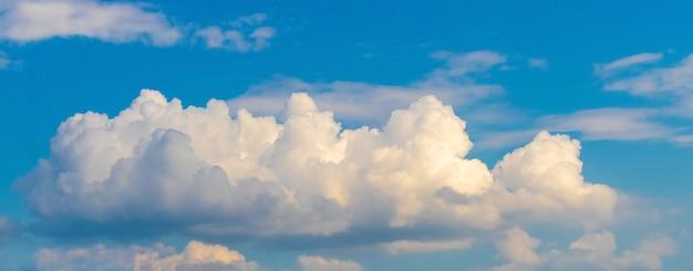 Witte krullende wolk in de blauwe lucht verlicht door de avondzon