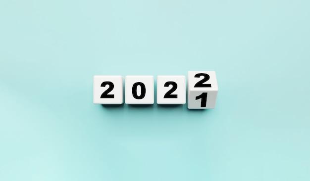 Witte kubusblok flipping van 2021 tot 2022 op blauwe achtergrond, voorbereiding op prettige kerstdagen en gelukkig nieuwjaar en 3d-renderingconcept.