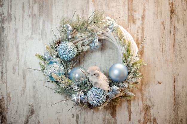 Witte kunstkrans van kerstmis met lichtblauwe decoratie en kleine speelgoeduil