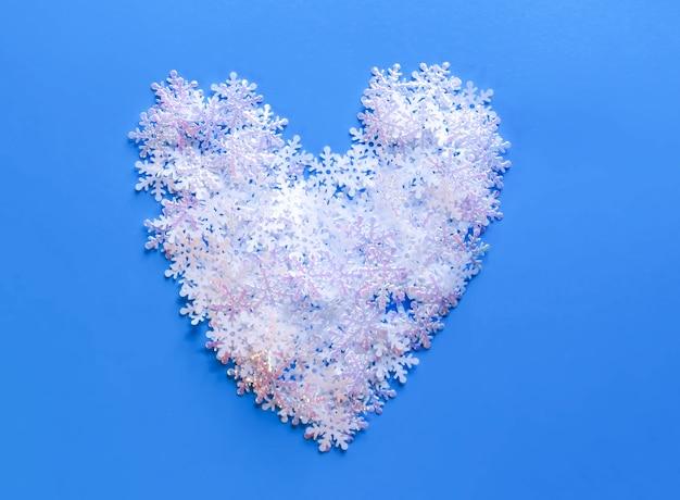 Witte kunstmatige sneeuw in vorm van hart op blauwe achtergrond. winterse achtergrond.