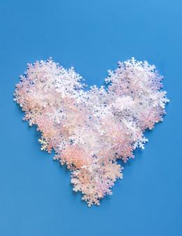 Witte kunstmatige sneeuwvlokken in een vorm van hart op zachte blauwe achtergrond. winterse achtergrond. decoratieve sjabloon voor kaarten, spandoek, poster.