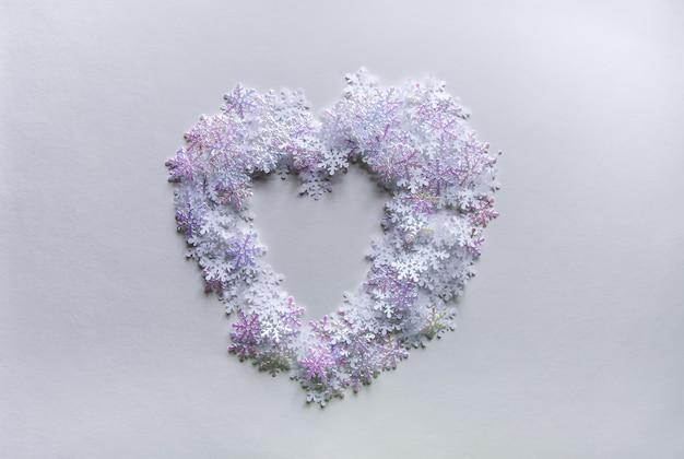 Witte kunstmatige sneeuwvlokken in een vorm van het hart op zachte lichte achtergrond. winterse achtergrond. decoratieve sjabloon voor kaarten, spandoek, poster.