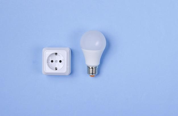 Witte kunststof stopcontact en led-gloeilamp op paarse achtergrond. minimalisme. bovenaanzicht