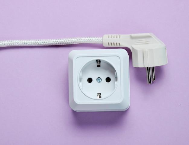Witte kunststof stopcontact en stekker op paarse tafel. bovenaanzicht