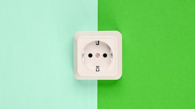Witte kunststof stopcontact op pastel achtergrond. minimalisme