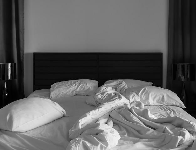 Witte laken en kussens in de donkere slaapkamer verknoeid