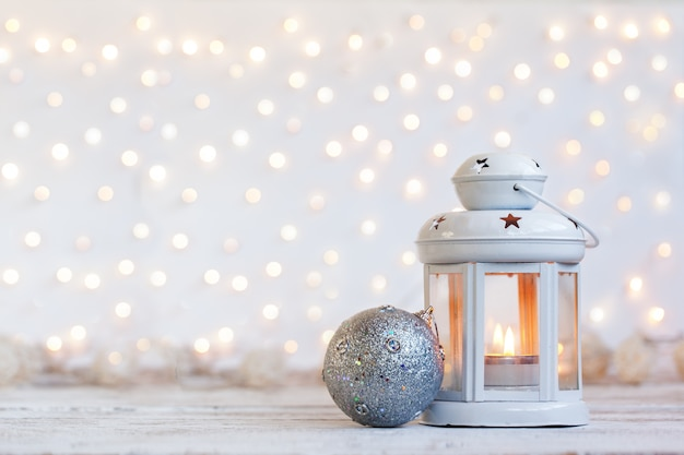 Witte lantaarn met kaars en zilveren bal - kerstdecoratie.