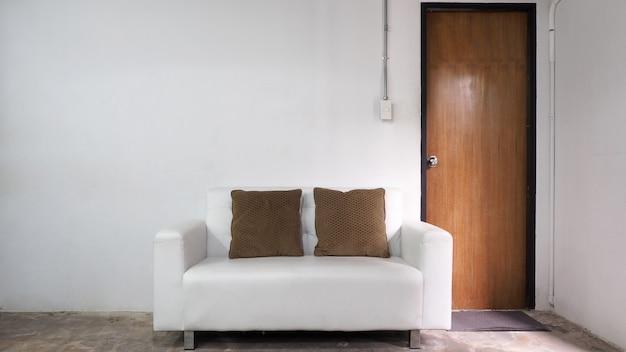 Witte lederen bank en witte oude muur en oude houten deur in de kamer.