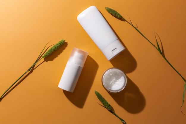 Witte lege cosmetische productenflessen op oranje achtergrond met vrije ruimte voor tekst als advertentie