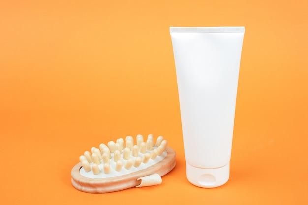 Witte lege cosmetische tube crème of bodylotion en houten anti-cellulitis stimulator. concept strijd tegen cellulitis.