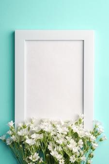 Witte lege fotolijst met muis-oor vogelmuur bloemen op blauwe achtergrond, bovenaanzicht kopie ruimte