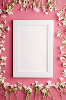 Witte lege fotolijst met muis-oor vogelmuur bloemen op roze paarse tafel, bovenaanzicht kopie ruimte