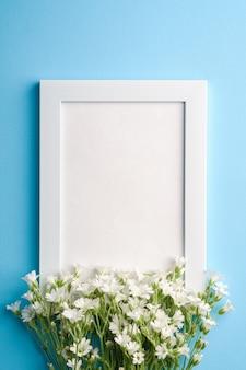Witte lege fotolijst mockup met muis-oor vogelmuur bloemen op blauwe achtergrond, bovenaanzicht kopie ruimte
