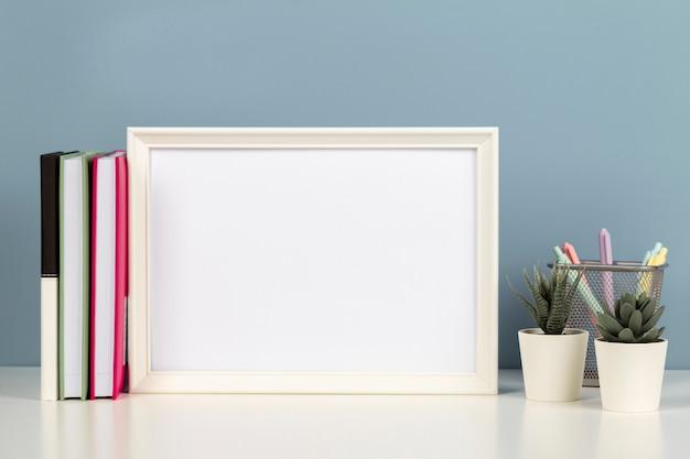 Witte lege houten mock-up frame op wit bureau met papieren notitieboekje boeken bloemen thuis