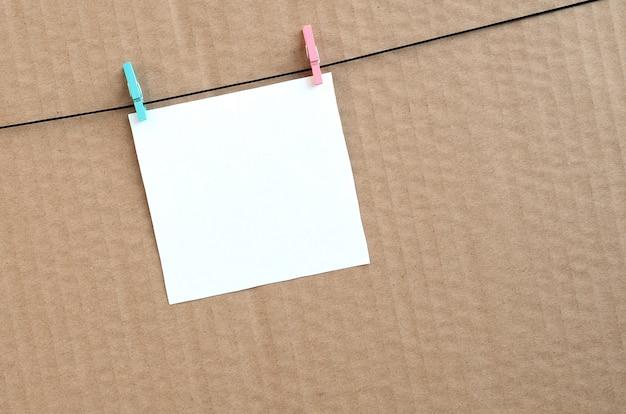 Witte lege kaart op touw op een bruine kartonnen achtergrond.