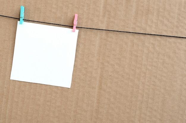 Witte lege kaart op touw op een bruine kartonnen achtergrond