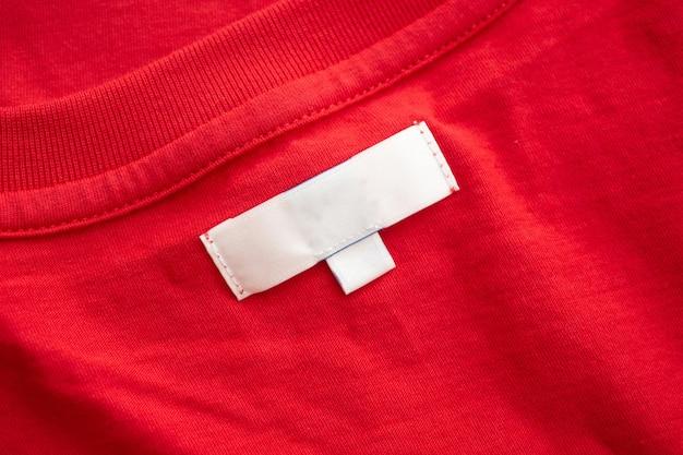 Witte lege kleding label label op nieuwe rode katoenen shirt stof textuur achtergrond
