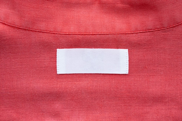 Witte lege kleding label label op rode linnen overhemd stof textuur achtergrond Premium Foto