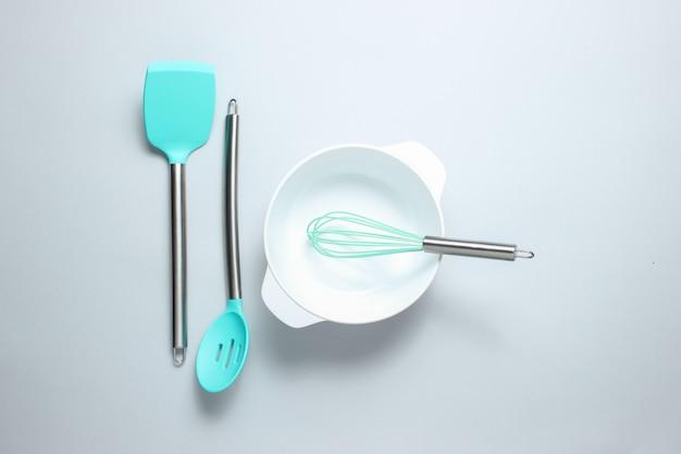 Witte lege kom met garde met spatel om te koken, pollepel op grijze tafel. bovenaanzicht, minimalisme