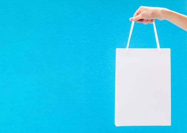 Witte lege papieren zak met handvatten op blauw