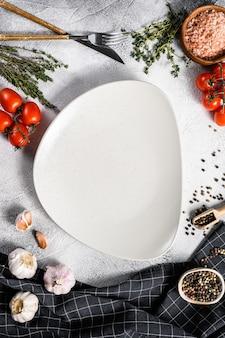 Witte lege plaat in het centrum van verse rauwe groenten, groenten. gezond, schoon eten, veganistisch, dieetvoedselconcept. witte achtergrond