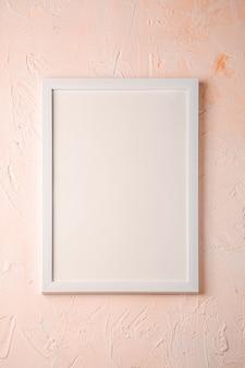 Witte lege sjabloon afbeeldingsframe op getextureerde helder, crème en perzik oppervlak, bovenaanzicht, mockup kopie ruimte