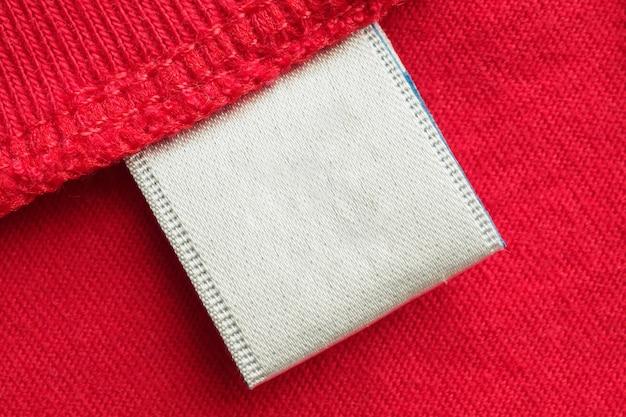 Witte lege wasgoed zorg kleding label op rode katoenen shirt achtergrond Premium Foto