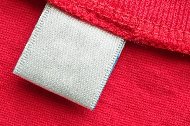 Witte lege wasgoed zorg kleding label op rode katoenen shirt achtergrond