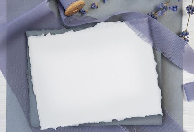 Witte lege wenskaart op een achtergrond van blauwe stof met lavendel bloemen