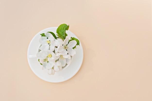 Witte lente appelboom bloeiende bloemen in een koffiekopje op een beige achtergrond. lente zomer concept. wenskaart. kopieer ruimte. plat liggen.