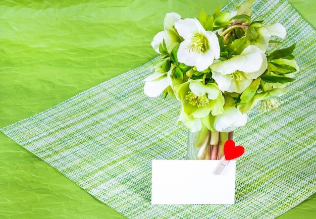 Witte lentebloemen op groene tafel en wenskaart met hart