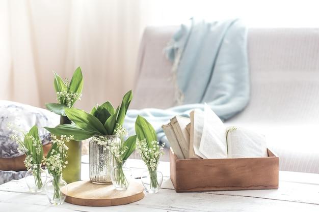 Witte lentebloemen sneeuwklokjes in vintage glazen flessen op witte houten tafel, cottage interieurdecoratie
