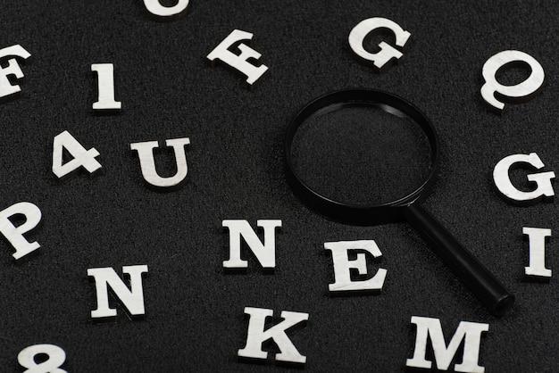Witte letters en cijfers en vergrootglas op zwarte achtergrond. zoek concept